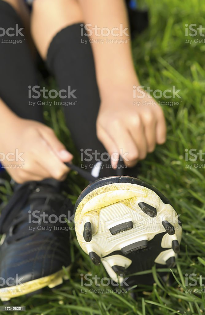 Young boy fixing his soccer shoes royalty-free stock photo