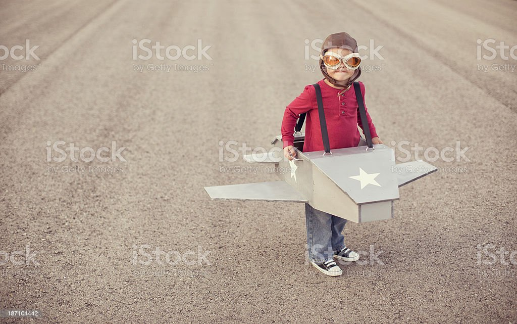 Young boy flying a cardboard airplane stock photo
