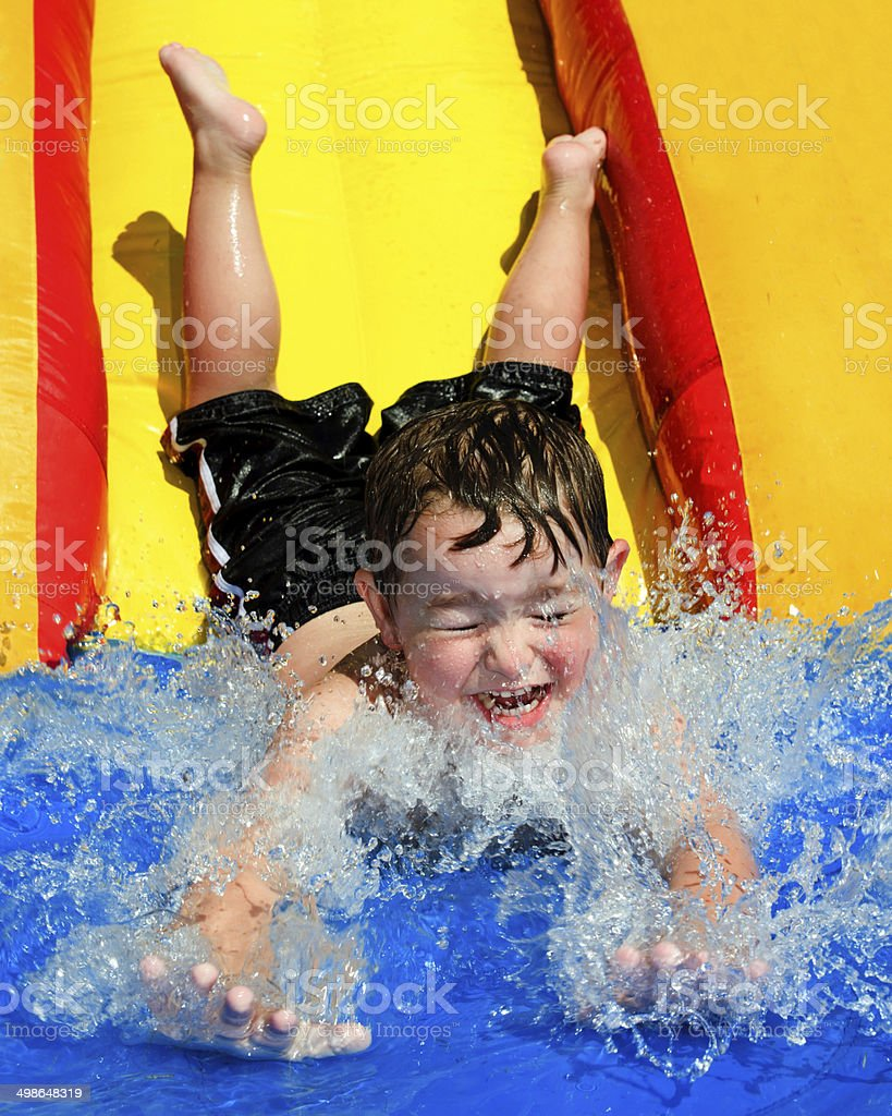 Young boy flying down water slide stock photo