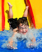 Young boy flying down water slide