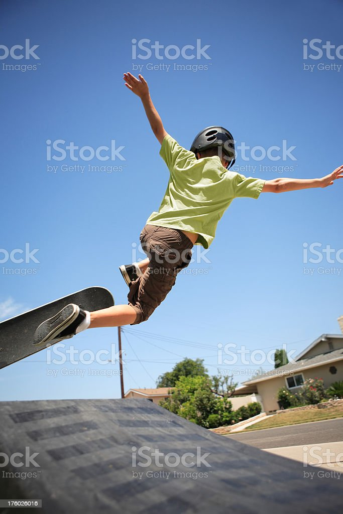 Young boy flying off skateboard royalty-free stock photo
