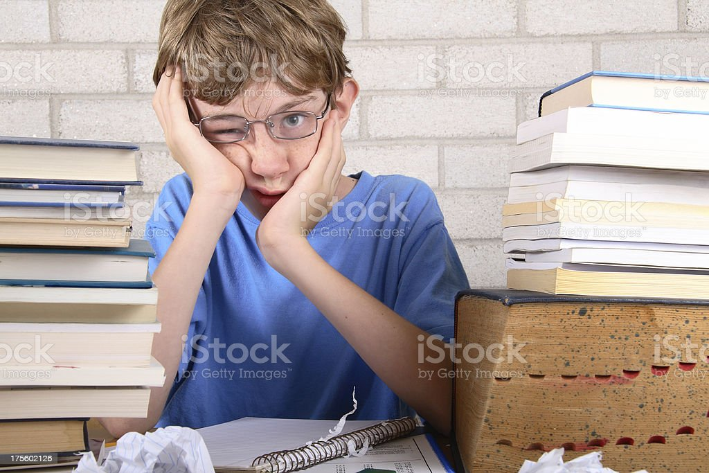 Young boy frustrated with stacks of books royalty-free stock photo