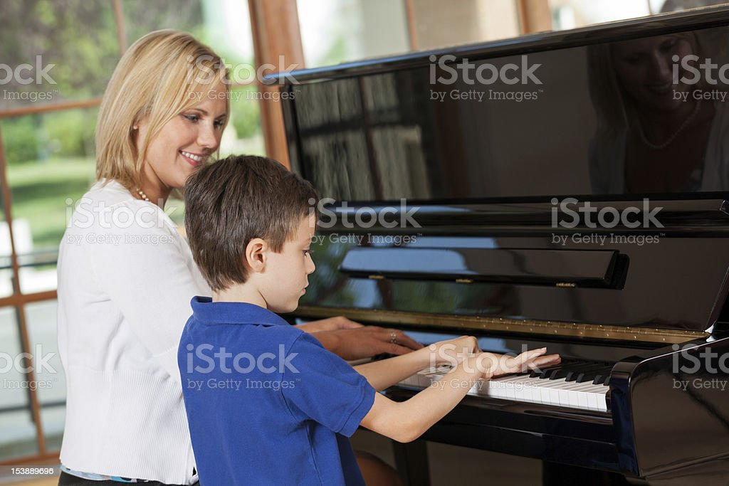 A young boy getting piano lessons stock photo
