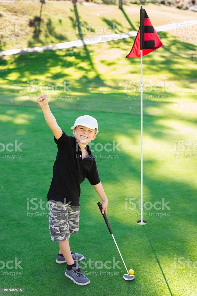 Young Boy Golfer Celebrating During Sunset stock photo