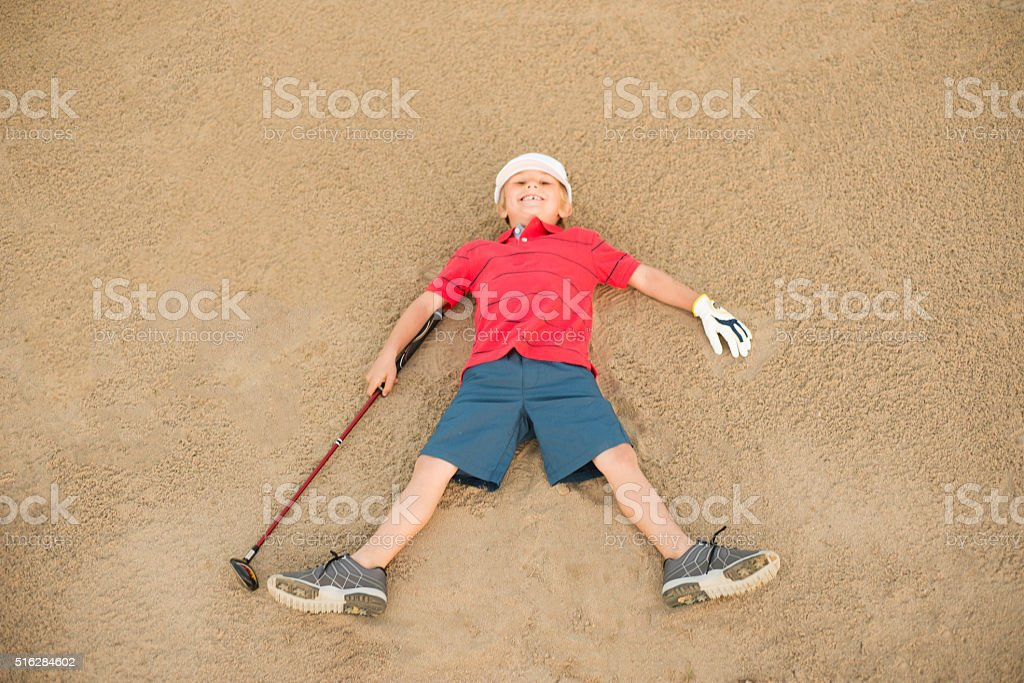 Young Boy Golfer Laying In A Sand Bunker Having Fun stock photo
