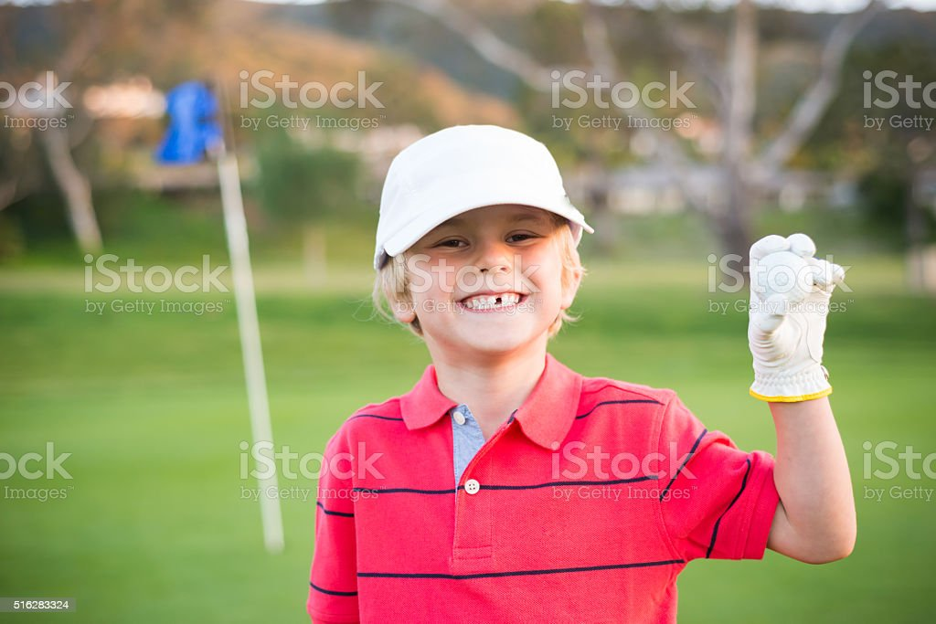 Young Boy Golfer On The Putting Green stock photo