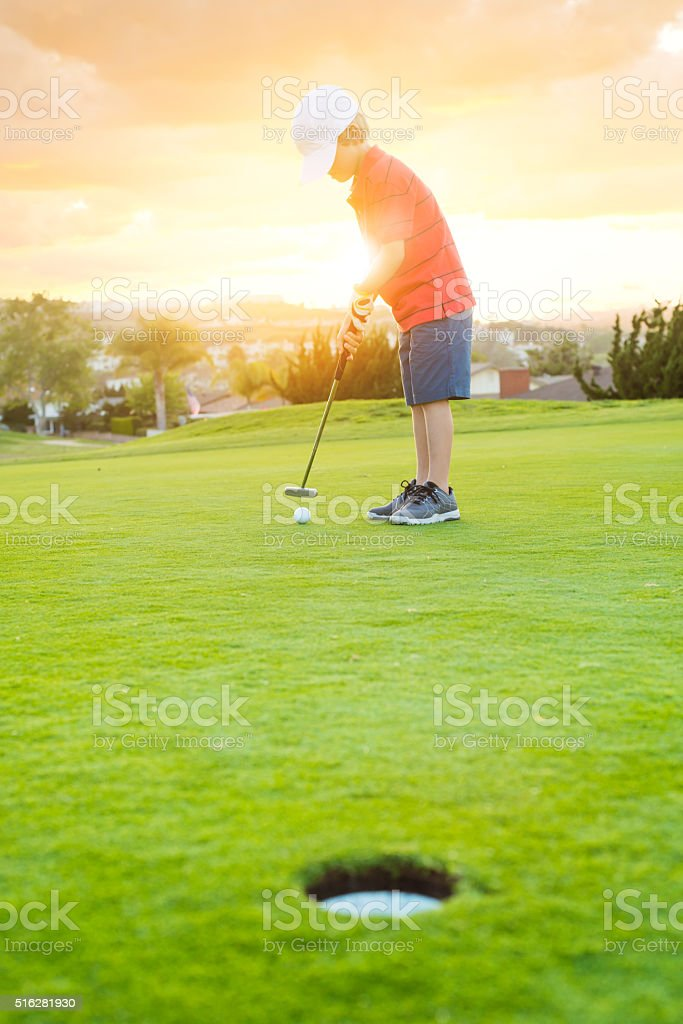 Young Boy Golfer Putting During Sunset stock photo