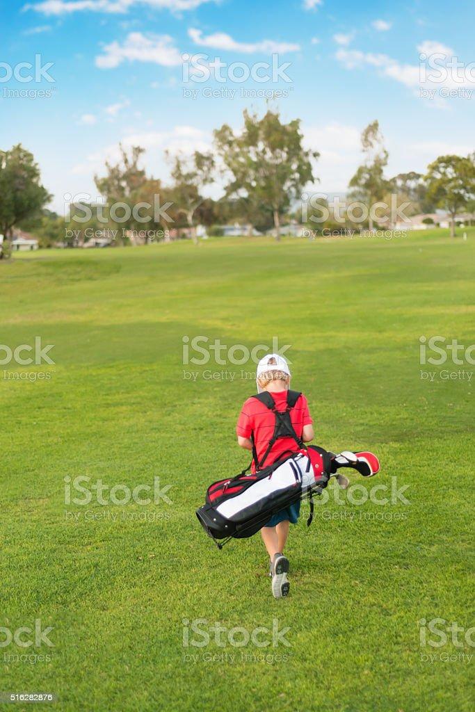 Young Boy Golfer Walking Down the Fairway stock photo