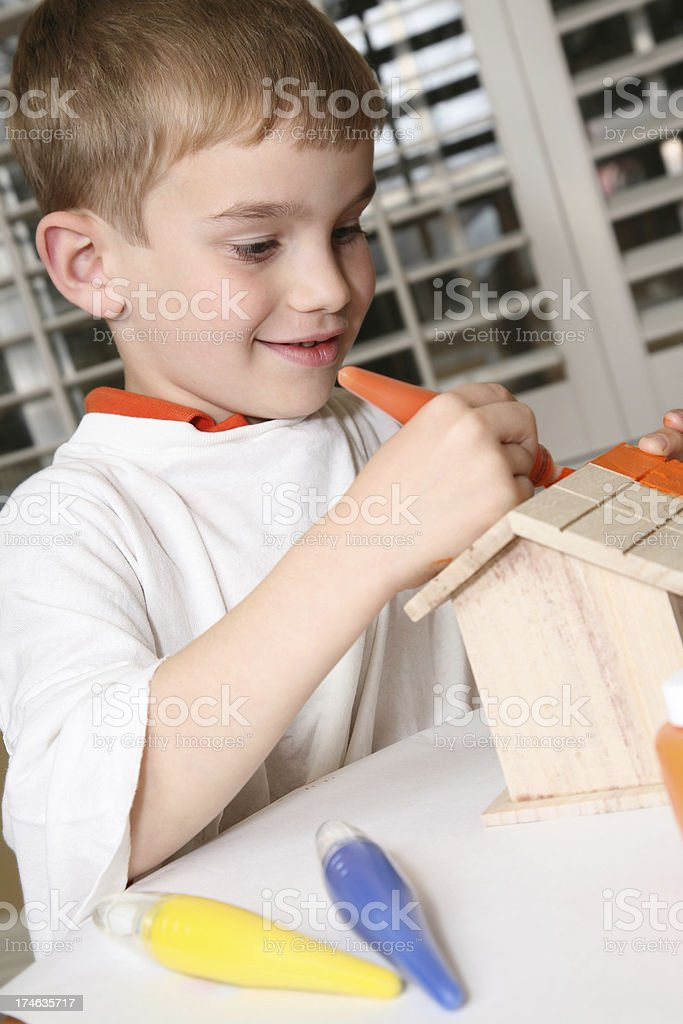 Young Boy Happily Painting a Bird House royalty-free stock photo