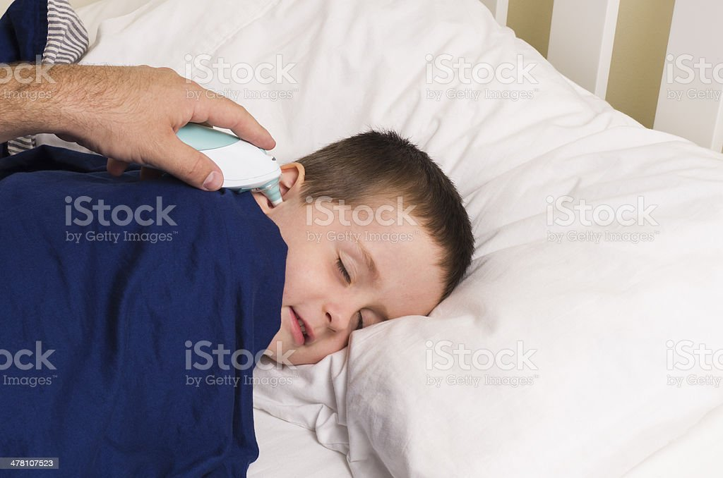 Young boy has his temperature taken with a digitial thermometer stock photo
