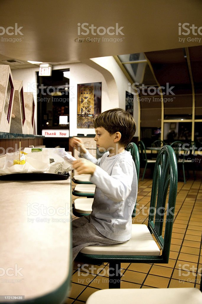 Young Boy Having a Late Night Meal at Fast Food Restaurant royalty-free stock photo