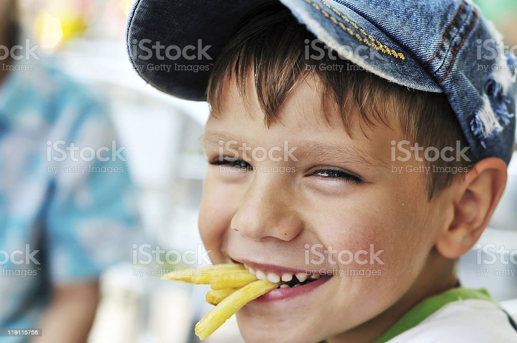 Young boy having a tasty French fry snack stock photo