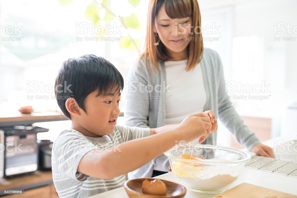 Young boy helping his mother in the kitchen stock photo