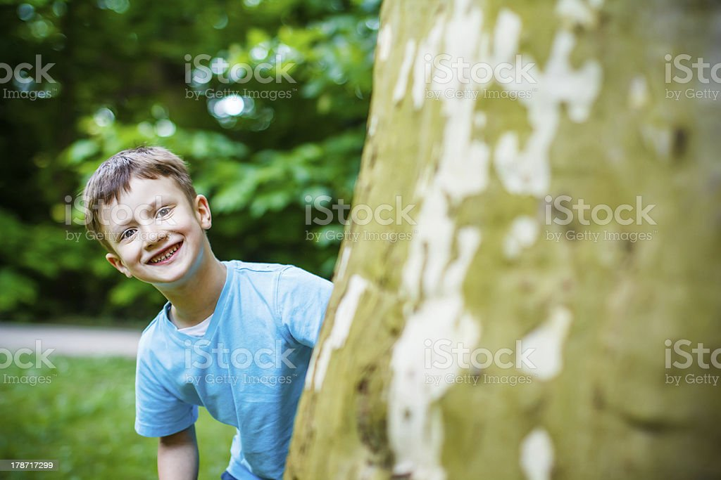 Young boy hiding at tree royalty-free stock photo