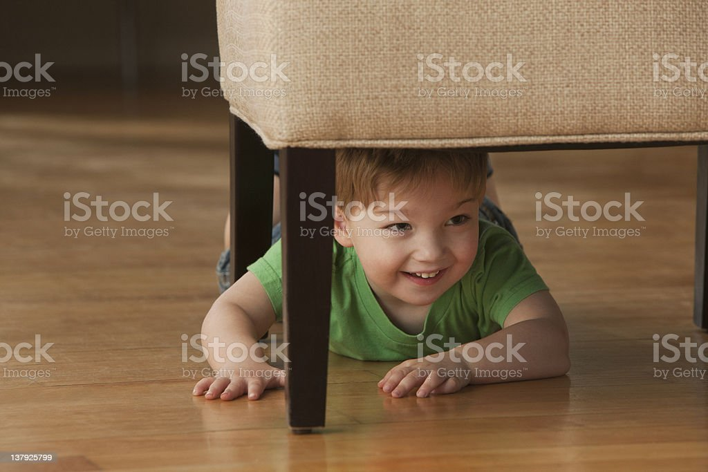 Young boy hiding underneath chair stock photo