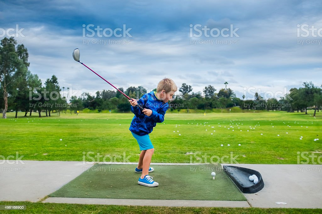 Young Boy Hitting A Golf Ball At The Range stock photo