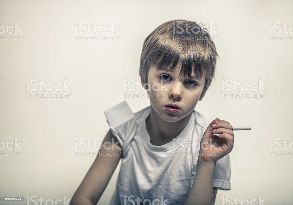 Young boy holding a cigarette royalty-free stock photo