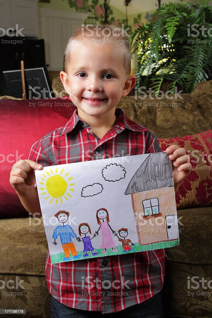 Young boy holding a family drawing at home stock photo