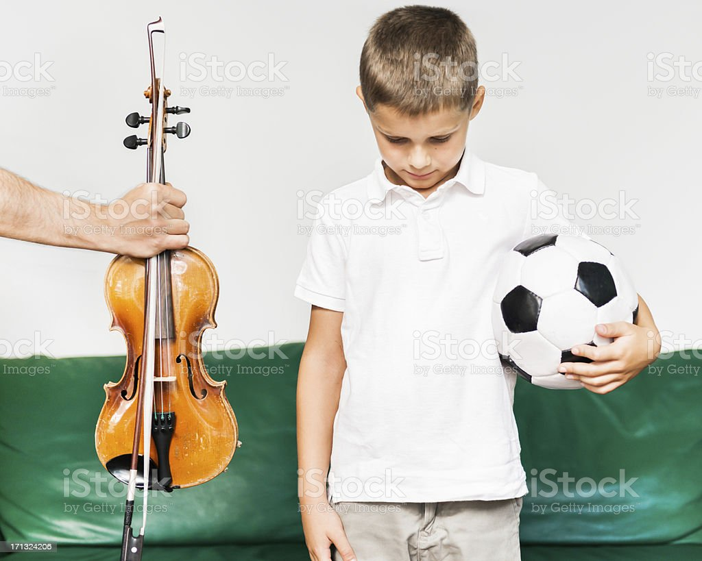 young boy holding a football and being handed a violin royalty-free stock photo
