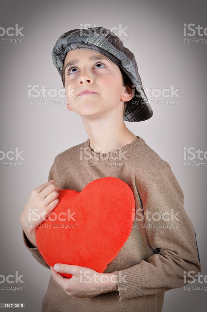 Young boy holding a plush red heart stock photo