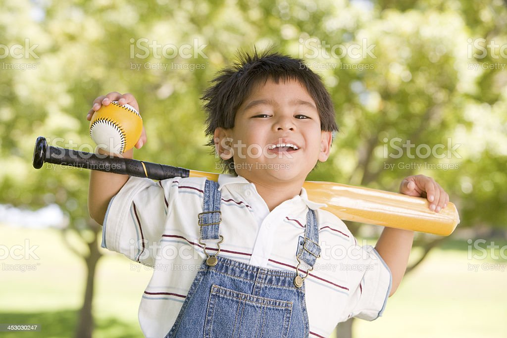 Young boy holding baseball bat outdoors smiling royalty-free stock photo
