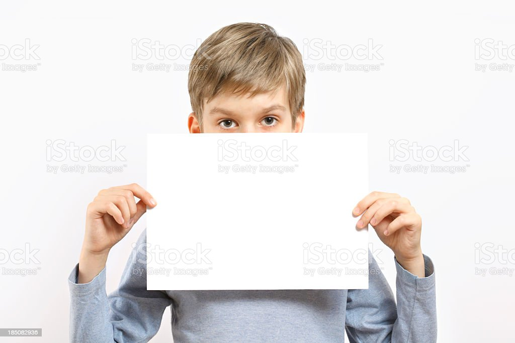 Young boy holding blank sheet of paper stock photo