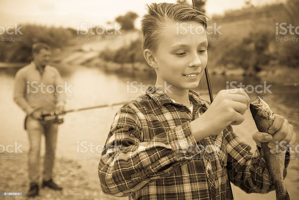 Young boy holding on hook fish on forest stock photo