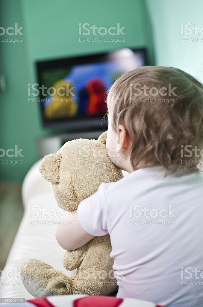 A young boy holding onto a teddy bear while watching TV stock photo