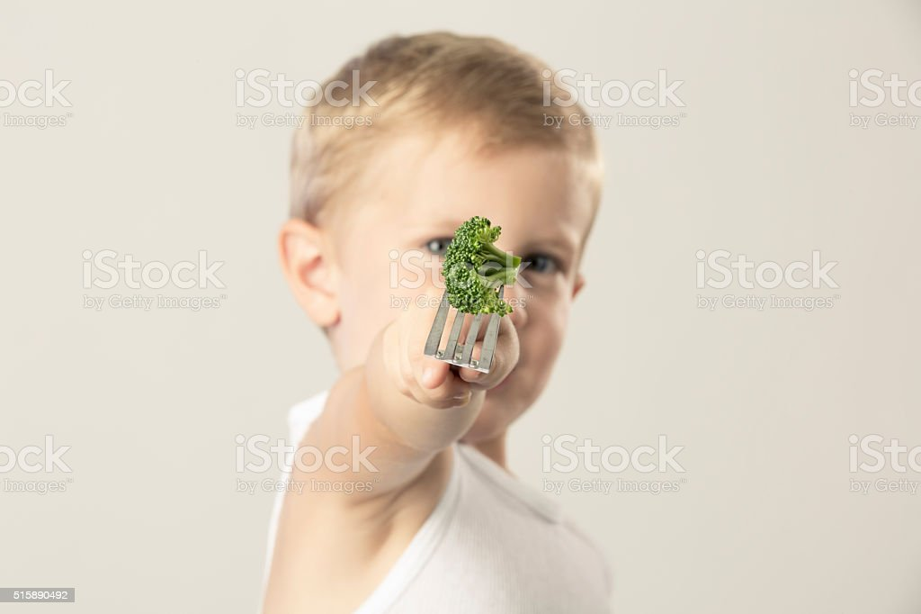Young Boy Holding out a Fork with Broccoli stock photo
