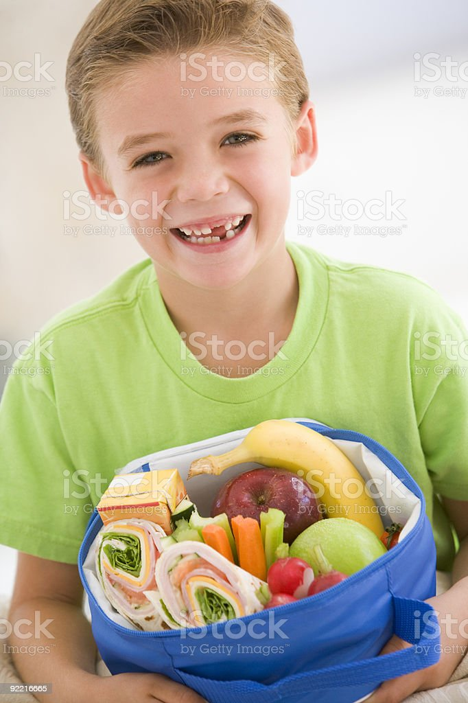Young boy holding packed lunch stock photo