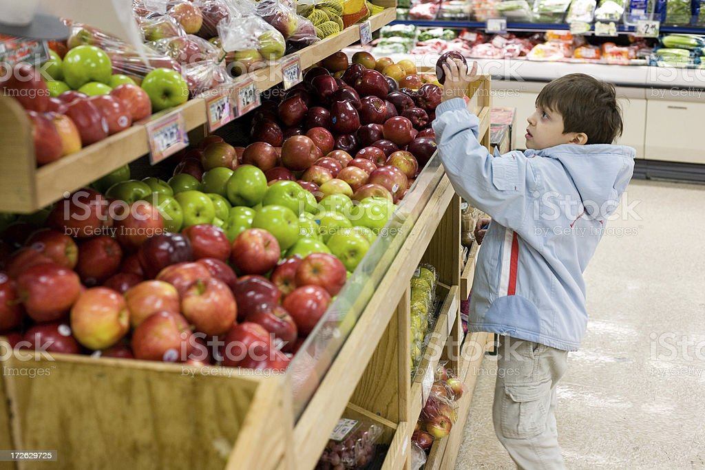 A young boy holds a red apple in a store stock photo