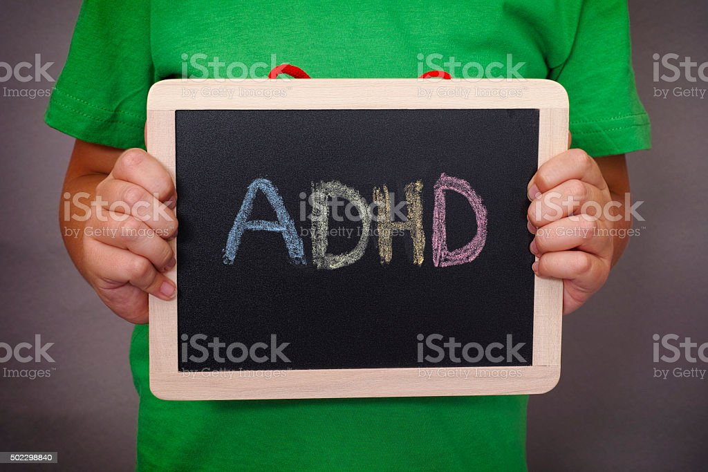 Young boy holds ADHD text written on blackboard stock photo