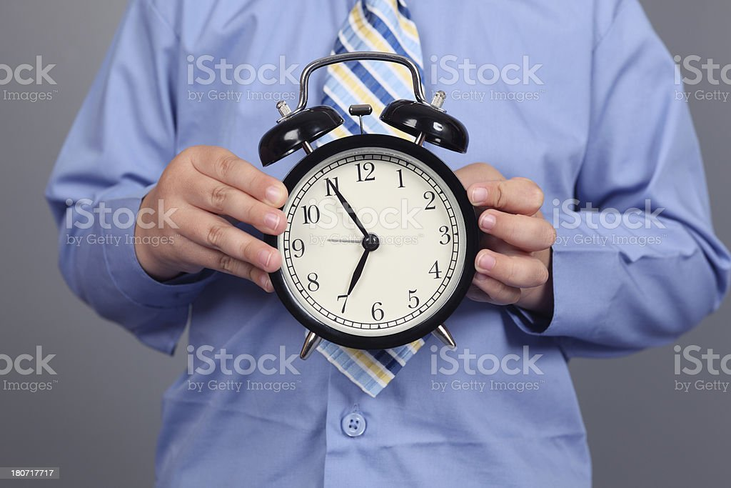 Young boy holds alarm clock royalty-free stock photo