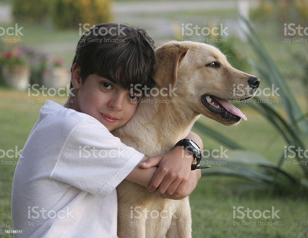 Young boy hugs his yellow Laborador dog outside royalty-free stock photo