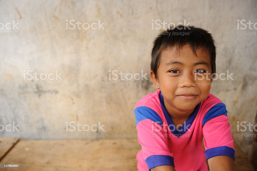 Young boy in a blue and pink shirt sitting on a bench stock photo