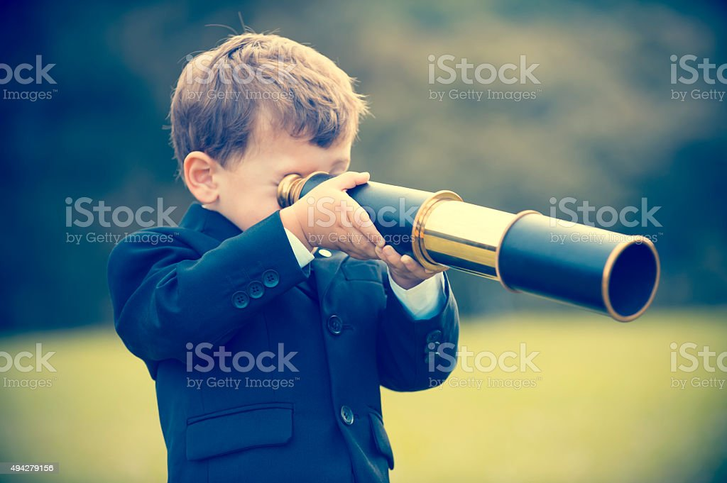 Young boy in a business suit with telescope. stock photo