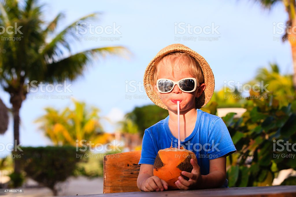 Young boy in a hat drinking out of a coconut on the beach stock photo