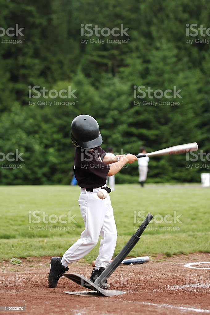 Young boy in a sports uniform slugging a baseball stock photo