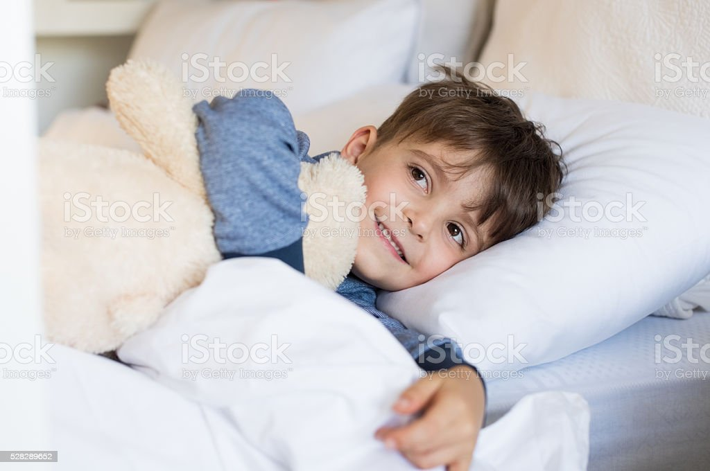 Young boy in bed stock photo