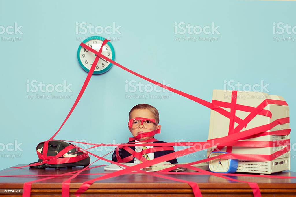 Young Boy in Business Office is Covered in Red Tape stock photo