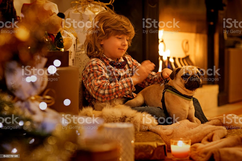 Young boy in christmas scene with festive decorations in indoor setting stock photo