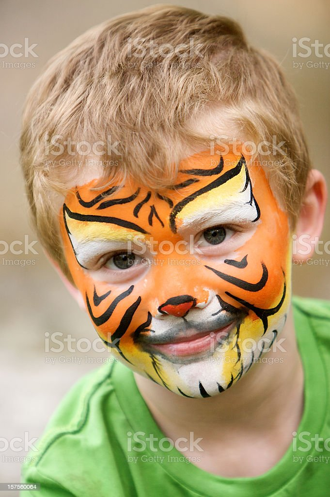 Young boy in green shirt with tiger face paint royalty-free stock photo