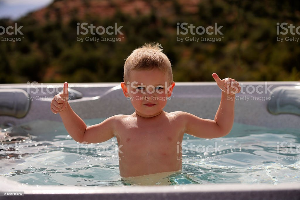 Young boy in hot tub giving thumbs up stock photo