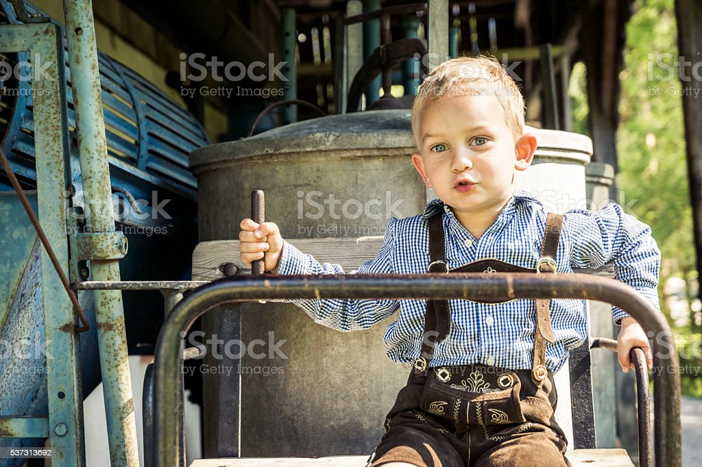 Young Boy in Lederhosen Playing on Old Steam Wagon stock photo