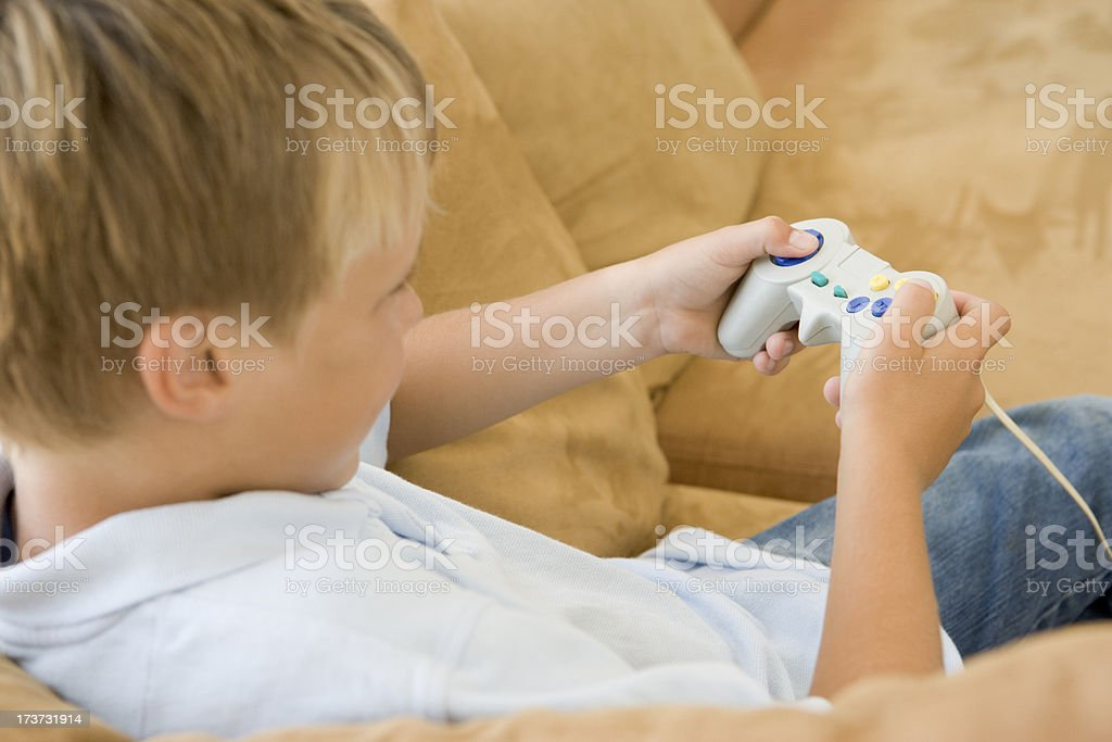 Young boy in living room with video game controller royalty-free stock photo