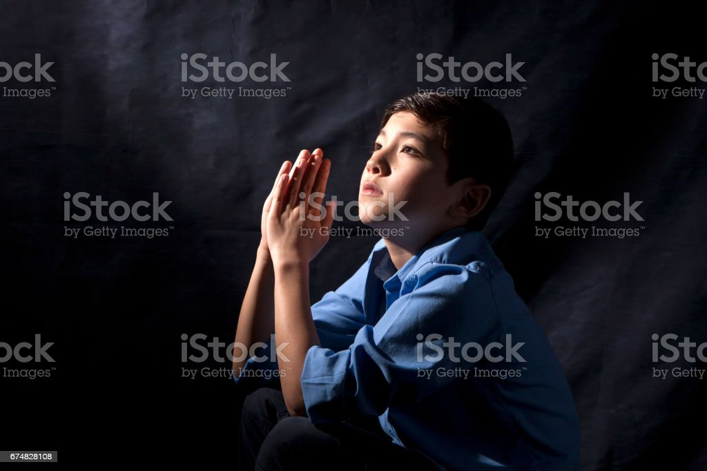 Young boy in prayer. stock photo