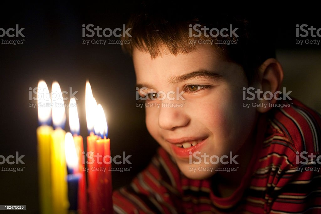 A young boy in red about to blow out his birthday candles royalty-free stock photo