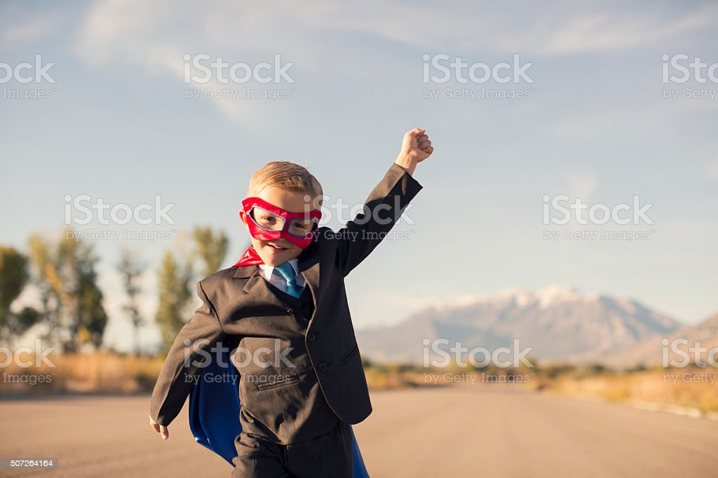 Young Boy in Superhero Costume and Business Suit is Running stock photo
