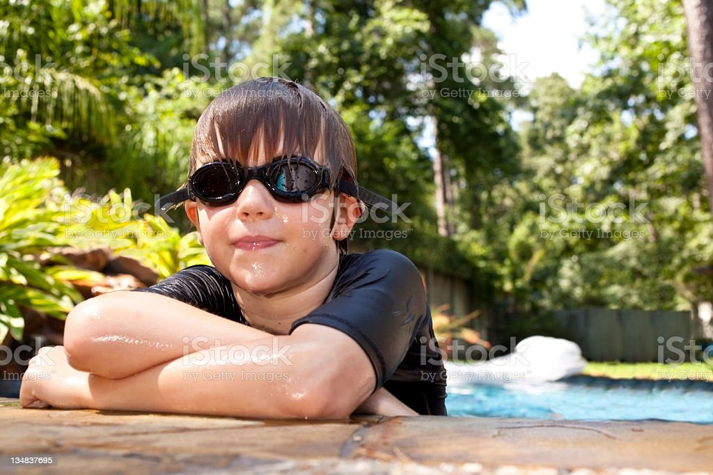Young boy in swimming pool wearing goggles royalty-free stock photo