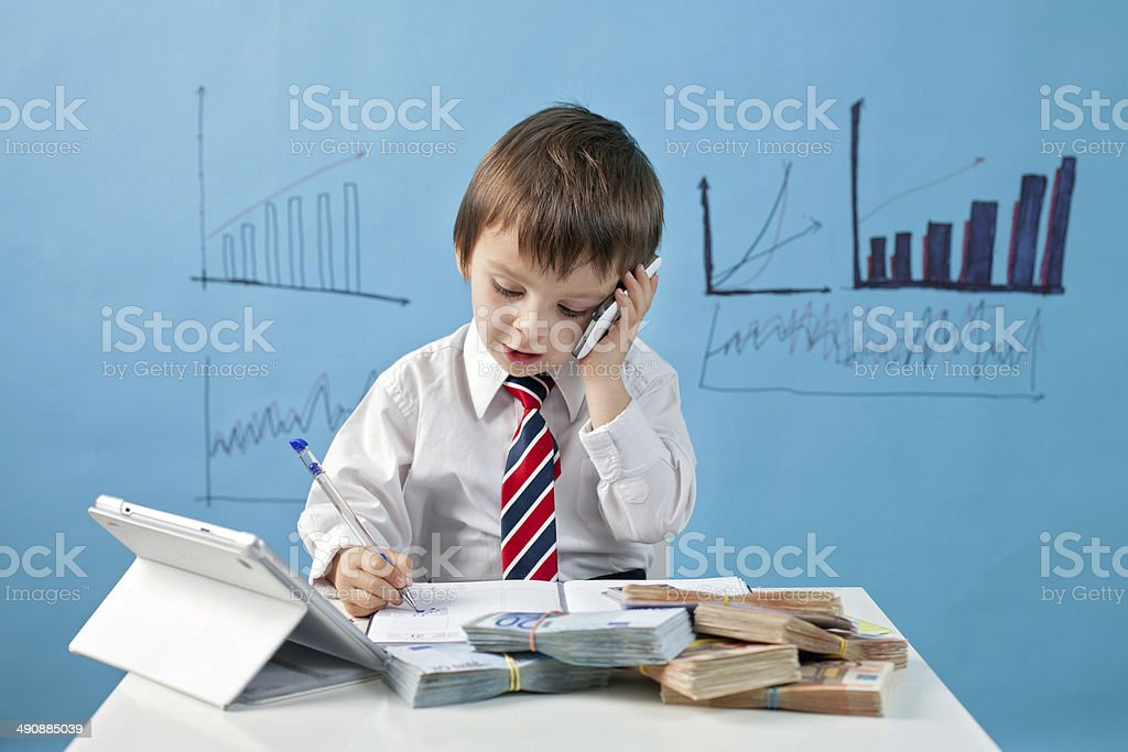 Young boy in tie with phone, notebook and money stock photo